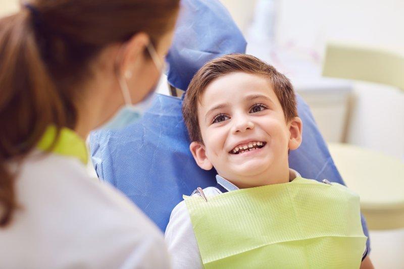 Little boy showing baby teeth to dentist